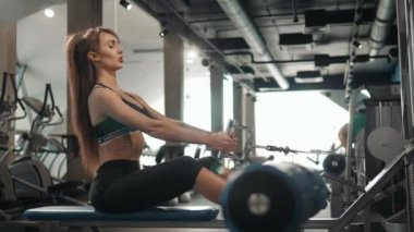 young sport woman girl athlete having hard workout on rowing machines in gym. Brunette sexy beautiful fit healthy female indoor training