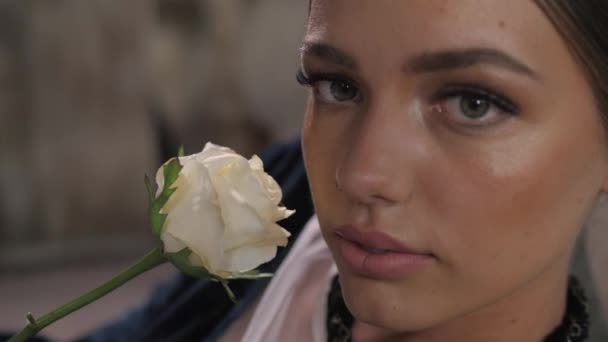 Close-up shot of sexy woman lips with lipstick and beautiful white rose sensual