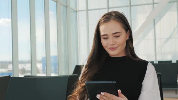 Cestující cestující žena letišti čeká na letecké dopravy pomocí tabletu, chytrého telefonu. Mladá podnikatelka usmívající se sezení s cestovní kufr vozík, v tertminal sále odletové haly v čekání