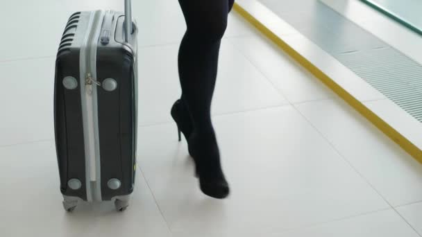 Zblízka se ženy kufrem na letištní terminál a spěchá za změnami na dovolenou nebo služební cestu. Happy podpatky