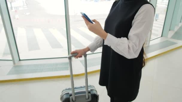 Turistické žena v mezinárodní letištní terminál se zavazadly pomocí chytrého telefonu. Hlasové rozpoznávání textu zprávy příkaz Pomocník