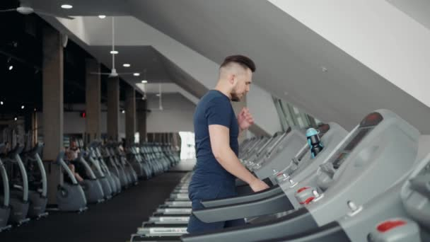 Young man in sportswear running on treadmill at gym, start prepare training workout
