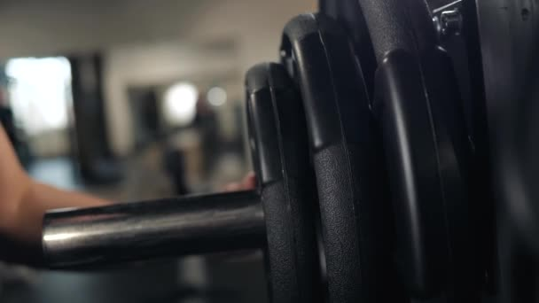 close up of handsome bodybuilder guy prepare to do exercises with barbell in a gym, keep barbell plate in hands macro super