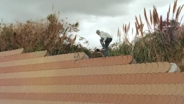 Skateboarder doing dangerous stall trick on street, skater man perform extreme big gap professional skateboard jump
