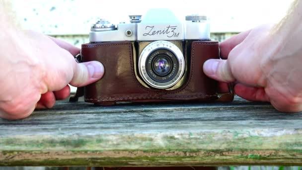 fotograf upraví objektivu historickou značku fotoaparátu Zenit 3m
