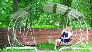 A girl in a blue dress sits on a historic swing under the vault of green trees