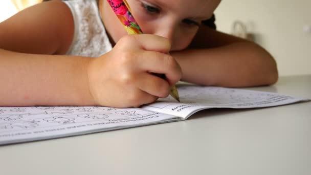 a hallgató írja egy golyóstoll számokat és a betűket az iskola jegyzetfüzetben