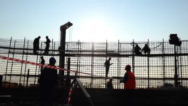 pracovník v přilbě roztáhne ochrannou pásku na staveništi