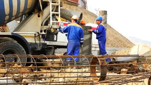 Arbeiter auf der Baustelle erhalten Beton von einem Betonmischer und werden in eine Hülle in eine Hülle gegossen