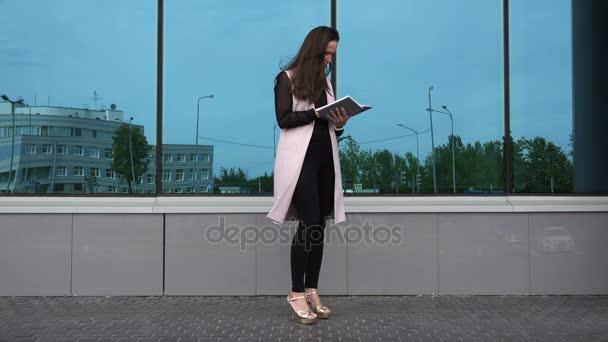 brunetka v růžové sako listoval deník