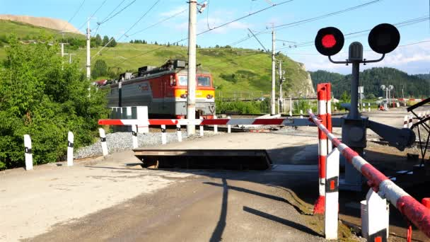 freight train passes by a closed railway crossing