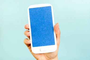 Hand showing blue screen vertical mobile paper concept on blue background