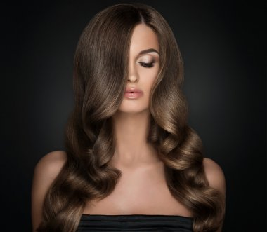 girl with long  and   shiny wavy hair .