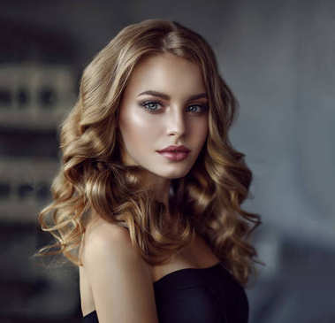 girl with long  and   shiny curly hair .