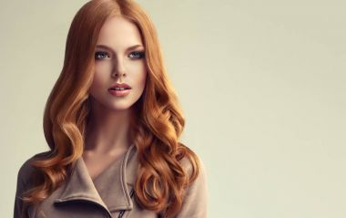 red hair  girl with long  and   shiny curly hair .  Beautiful  model woman  with curly hairstyle   .Care and beauty of hair