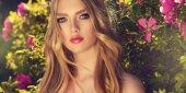Krásný jarní dívka voňavé růžové květy, v létě kvetoucí parku. Žena v kvetoucí zahradě. Móda, kosmetika  parfémy. Kudrnaté blond vlasy