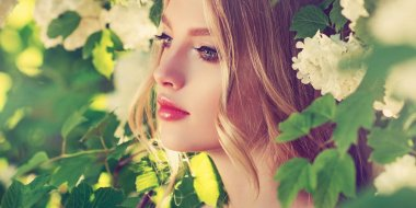 Beautiful spring girl in fragrant white flowers in summer blossom park. Woman in a blooming garden . Fashion, Cosmetics & Perfumes . Curly blonde hair