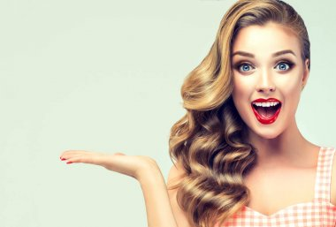 Woman surprise showing product .Beautiful girl pointing to the side . Presenting your product. Expressive facial expressions emotions