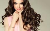 Fotografie Brunette dívka s kudrnatými vlasy dlouhé, zdravé a lesklé. Krásný model žena s vlnitý účes. Péče a krása
