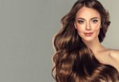 Krásná brunetka s dlouhými a lesklými vlnitými vlasy na čele. Krásná žena model s kudrnatý účes .