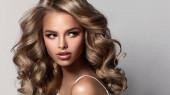 Szépségbarna lány hosszú és fényes hullámos hajjal. Gyönyörű nő modell göndör frizurával. Perm, trichológia és gondozás