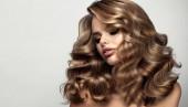 Krásná brunetka s dlouhými a lesklými vlnitými vlasy. Krásná žena model s kudrnatý účes. Permie, trichologie a péče