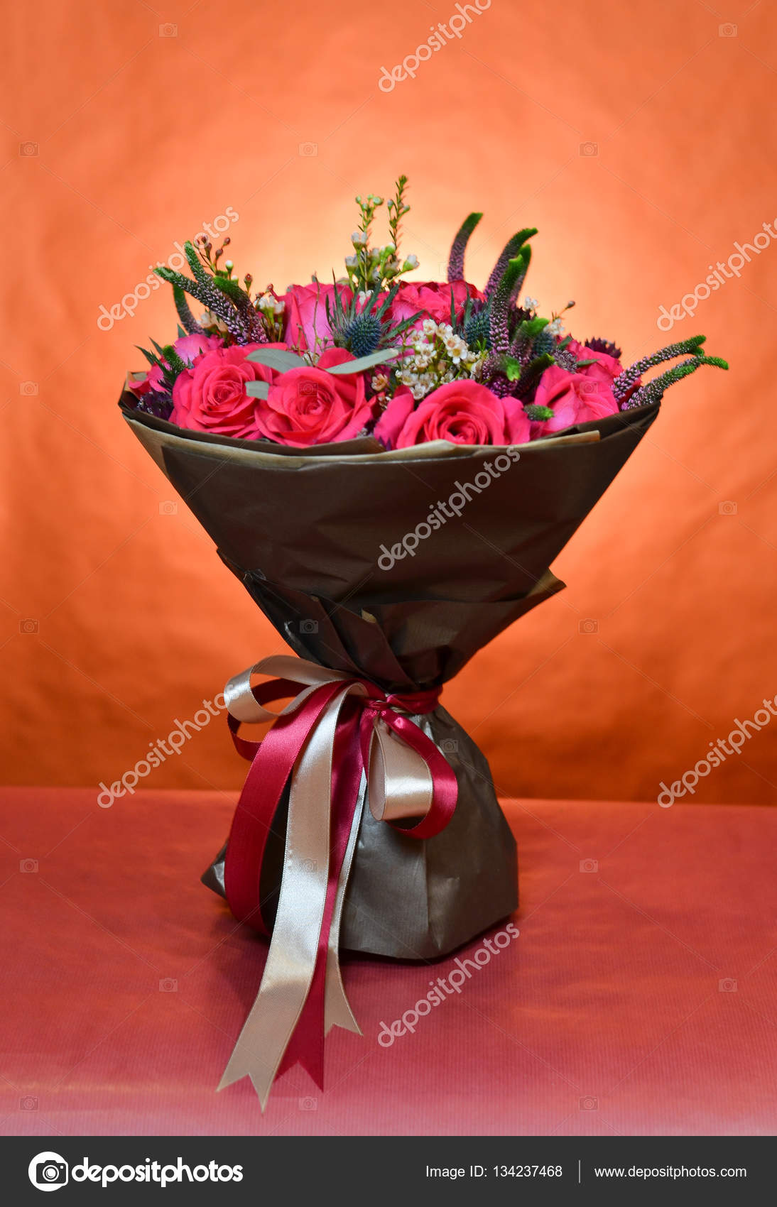 Bouquet Of Roses Wrapped In Brown Paper And Tied With Ribbons