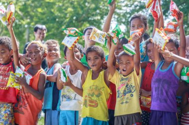 Filipino children standing in a line and holding snack in their