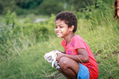 Portrait of Aeta tribe little girl with her cute cat near Mount