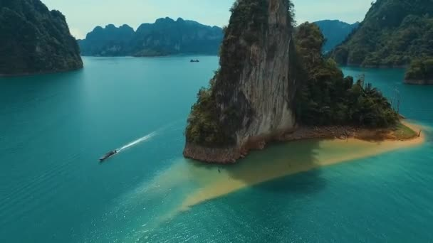 Aerial: The long tail boat and a lonley rock on the lake.