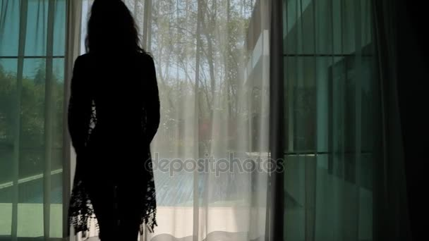 Mladá dívka otevírá závěsy v ložnici a do fondu