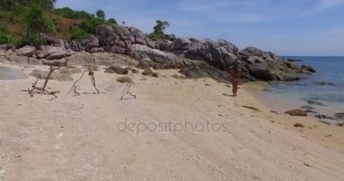 Aerial: Young lady is walking on the wild beach on the island. Thailand. Phuket.
