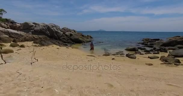Aerial: Young lady is posing on the beach among stones. Thailand. Phuket.