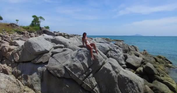 Aerial: Young lady is posing on the rocks on the wild beach. Thailand. Phuket.