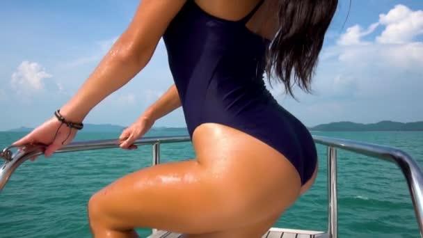 Krásná dívka pózuje na přídi jachty ve zpomaleném filmu. Výhled na moře.