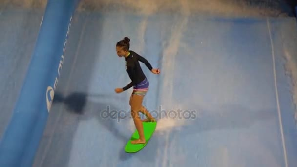 PHUKET, THAILAND May 12, 2017: The flow rider girl is surfing at surf machine. Slow motion.