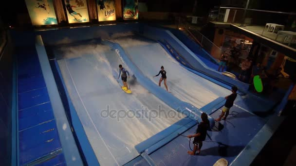 PHUKET, THAILAND May 12, 2017: Man and girl are flowboarding at surf machine.