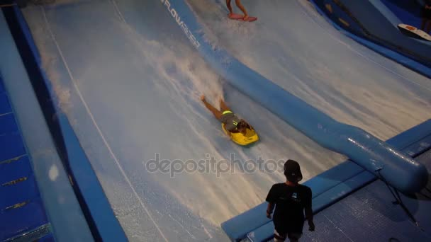 PHUKET, THAILAND May 12, 2017: Two girls are surfing at surf machine. Flowboard.