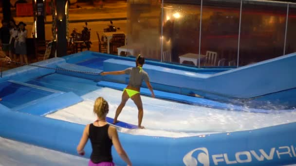 PHUKET, THAILAND May 12, 2017: Two girls are flowboarding at surf machine.