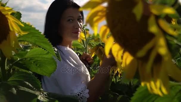 Dívka chodí v poli s slunečnice
