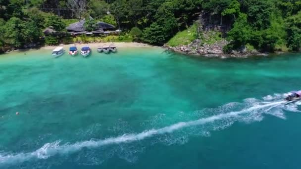 Aerial: Two boats leave from the Phi Phi Don beach.