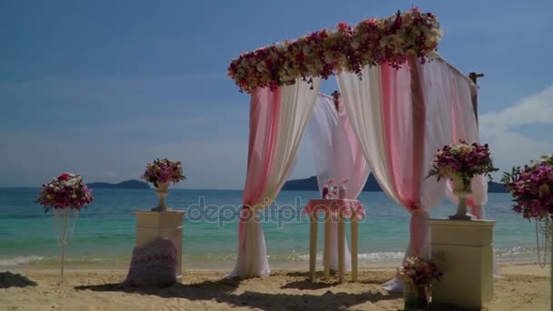 Beautiful wedding arch with flowers on the beach.