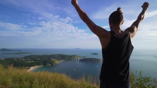 Athletic young man stands with his hands up on the edge of the mountain.