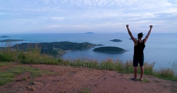 Aerial: Athletic young man stands with his hands up on the edge of the mountain.