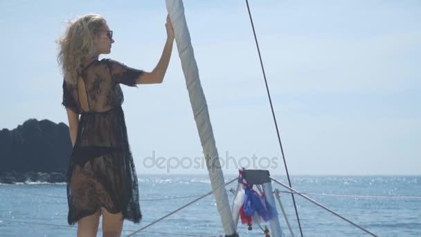 Ta blondýna stojí na přídi lodi a dívá na moři