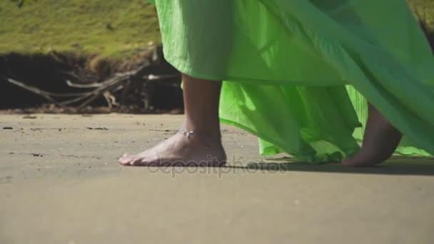 Lábát a lány séta a homokot egy zöld ruha.