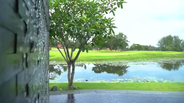 A wall waterfall in the pool with a view of the pond and a green golf course.