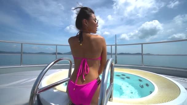 Asijská dívka v růžové plavky, sedí v plavkách na luxusní jachtě