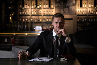 an elegant,serious and concentrated businessman holding a glass of whiskey and looking at camera