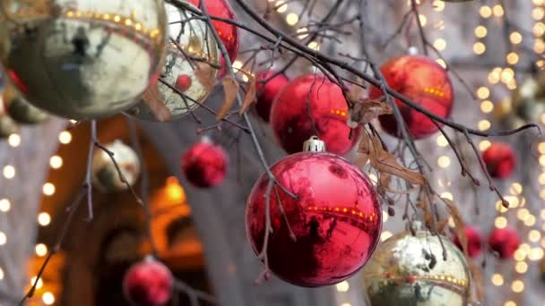Glossy bright red and golden baubles decorating trees outside